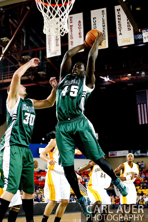11/24/2006 - Anchorage, Alaska: With teammate P.J. Owsley (30) looking on, Senior forward Ahmet Gueye (45) of the Hawaii Warriors grabs a rebound as California secures a birth in the championship game of the 2006 Great Alaska Shootout destroying  Hawaii 72-56<br />