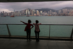 Two women viewing Hong Kong, China skyline and mountains across Victoria Harbor.