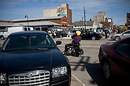 A man in a wheel chair passes cars at the Eastern market.  Eastern Market is a historic commercial district in Detroit. The Farmer's Market in Detroit was first opened in 1841 and still enjoys thousands of visitors every saturday. USA, 2011