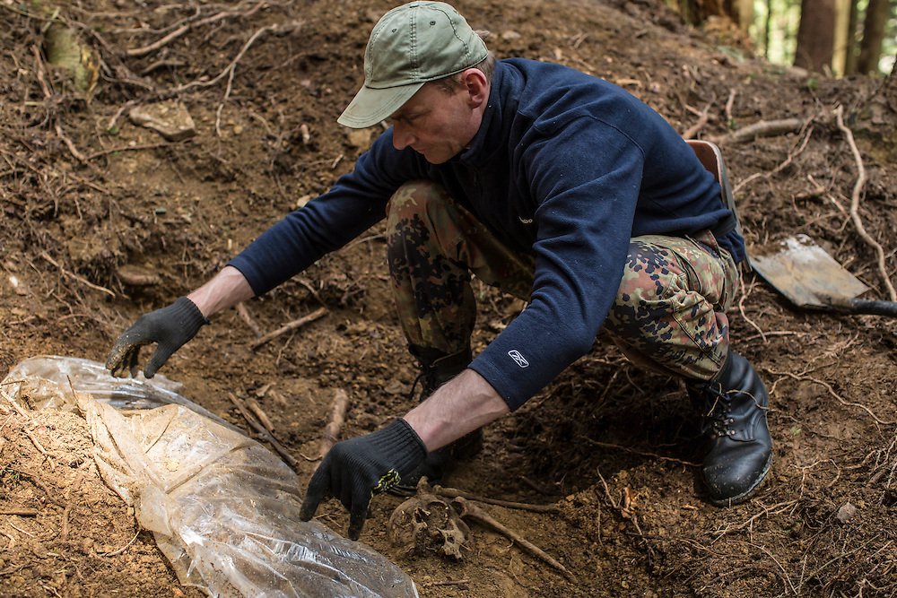 SKOLE, UKRAINE - MAY 1, 2015: Ostap Kozak, archivist for the organization Dolya, pulls back plastic sheeting to reveal a skeleton at the site of a World War II-era mass grave believed to contain the remains of Ukrainian partisans in Skole, Ukraine. Dolya was formed to excavate and repatriate remains from World War II, though its focus is often on locating the graves of Ukrainian partisans killed by Soviet forces. CREDIT: Brendan Hoffman for The New York Times