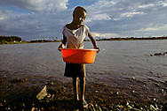 A Kenyan girl gets water from a local lake.