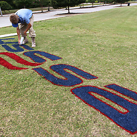 Justin Smedley puts the finishing touches on the USSSA logo near one of the entrances to the baseball complex as Ballard Park as they get the fields ready for the 12U State Baseball tournament.