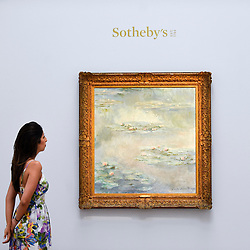 "© Licensed to London News Pictures. 14/06/2019. LONDON, UK. A staff member views ""Nymphéas"", 1908, by Claude Monet (Est. £25-30m). Preview of Impressionist and Modern art sales, which will take place at Sotheby's New Bond Street on 18 and 19 June 2019.  Photo credit: Stephen Chung/LNP"