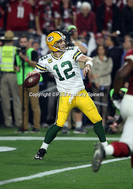 Green Bay Packers quarterback Aaron Rodgers (12) throws a 60 yard Hail Mary pass for a first down at the Arizona Cardinals 36 yard line on fourth down with 20 yards to go and under one minute left in the fourth quarter during the NFL NFC Divisional round playoff football game against the Arizona Cardinals on Saturday, Jan. 16, 2016 in Glendale, Ariz. The Cardinals won the game in overtime 26-20. (©Paul Anthony Spinelli)