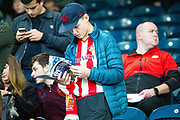 A Sunderland fan studies the match day programme before the EFL Sky Bet League 1 match between Rochdale and Sunderland at the Crown Oil Arena, Rochdale, England on 20 August 2019.