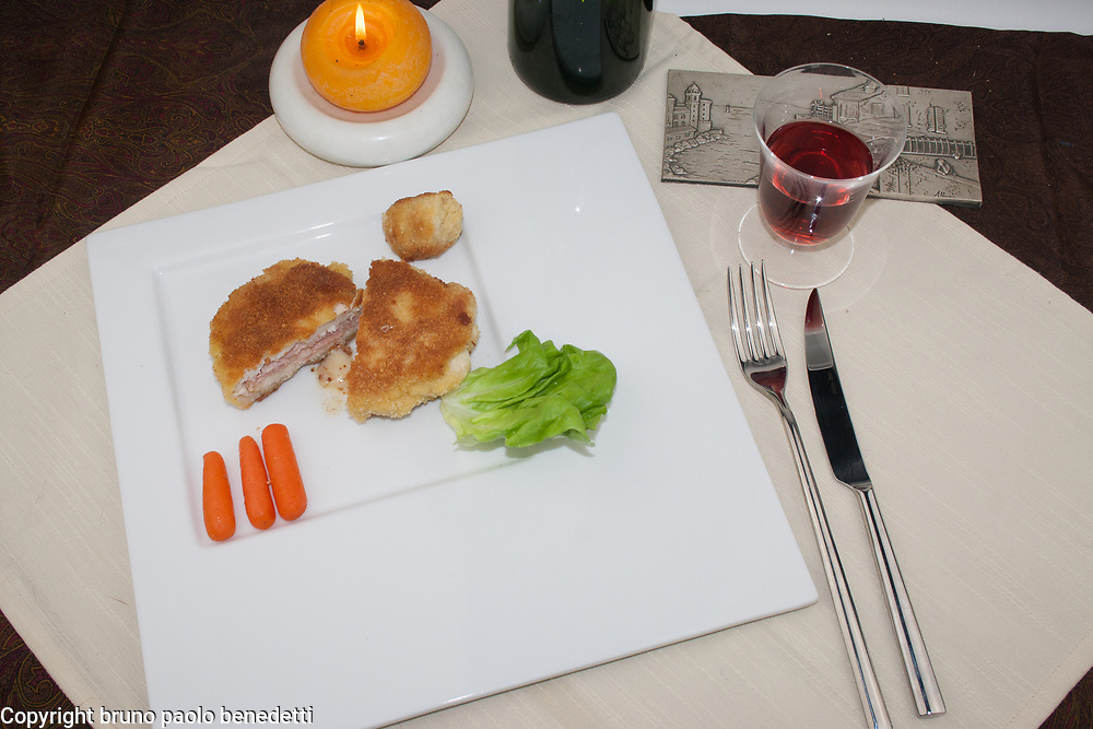 cordon bleu fried filled chicken breast side view from above on white dish with garnish, fork, knife, red wine and candle on white dish, frech cooking