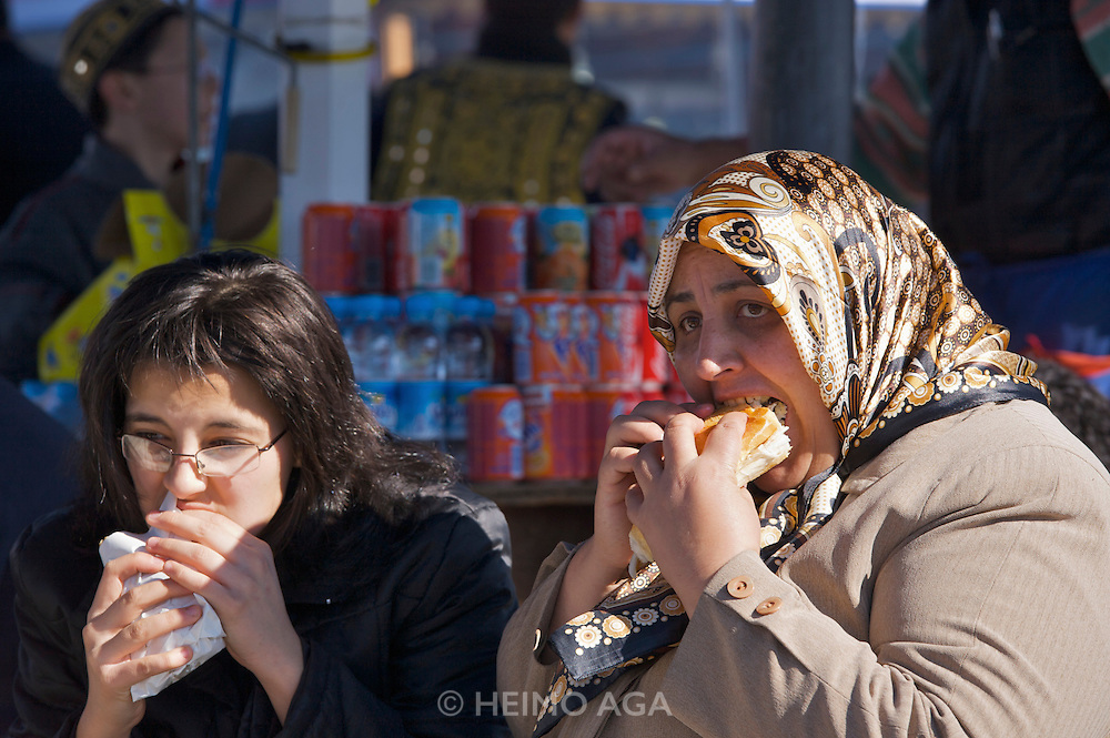 Istanbul. Ladies eating barbecued fish fresh from boats anchored on the Golden Horn (Halic?) near Galata Bridge.