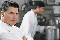 Male chef with colleague in kitchen portrait