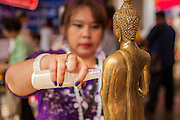 13 APRIL 2014 - BANGKOK, THAILAND: A woman bathes a Buddha statue in scented oils at Wat Chana Songkram in Bangkok. Many people go to temples and religious ceremonies to make merit on Songkran. Songkran is celebrated in Thailand as the traditional New Year's Day from 13 to 16 April. Songkran is in the hottest time of the year in Thailand, at the end of the dry season and provides an excuse for people to cool off in friendly water fights that take place throughout the country. Songkran has been a national holiday since 1940, when Thailand moved the first day of the year to January 1.    PHOTO BY JACK KURTZ