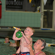 BRUNSWICK, Maine -- 6/24/13 -- Linda Blanton lifts her grandson, Calib Raines, 4, up to the pool hoop during the her annual swimming camp, held at Bowdoin College. Blanton, together with colleague Don Miskill, has created and led a early summer swimming program which teaches swimming and coaching leadership.  By bringing older children into positions of responsibility, she has trained thousands of children to swim. Using older children as trainers, she builds the next generation of swimming coaches and instructors. This year she manages over 200 swimmers and nearly as many volunteers.  She is in her fourth generation of coaches whom she's trained. Photo by Roger S. Duncan.