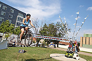A festival attendee takes a ride on artist Tim Scofield's Flying Bike during Artscape in Baltimore, MD on Saturday, July 20, 2013.