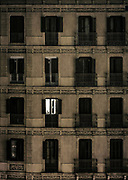 A single aparment light shines through the dark facade of a downtown building.