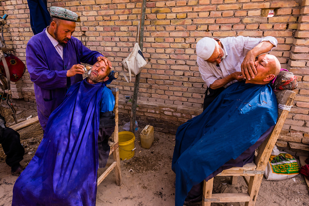Uyghur men getting a haircut and shave at the weekly market at Opal (Upal), a village along the Karokoram Highway (50 km. southwest of Kashgar) which follows the old Silk Road route from China to Pakistan, Xinjiang Province, China. Uyghur people are a Central Asian people of Muslim Turkic origin.