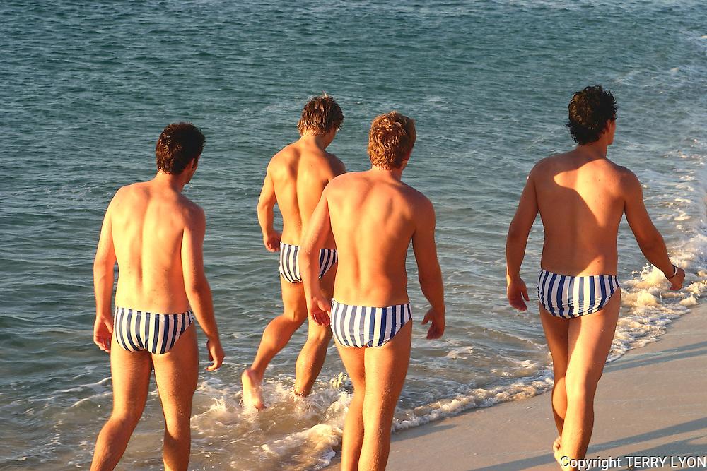 North Cottesloe surf club members walking on Cottesloe Beach.