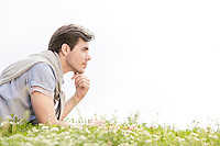 Side view of thoughtful young man lying on grass against clear sky