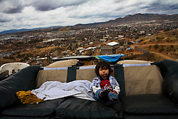 A young boy sits on a couch in Nogales. He and his family have been sleeping outside since their tin and cardboard shack burned to the ground two weeks before. Even before the accident the family had no water or electricity and their only source of income was selling scavenged trash.