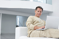 Man using laptop on sofa in living room portrait