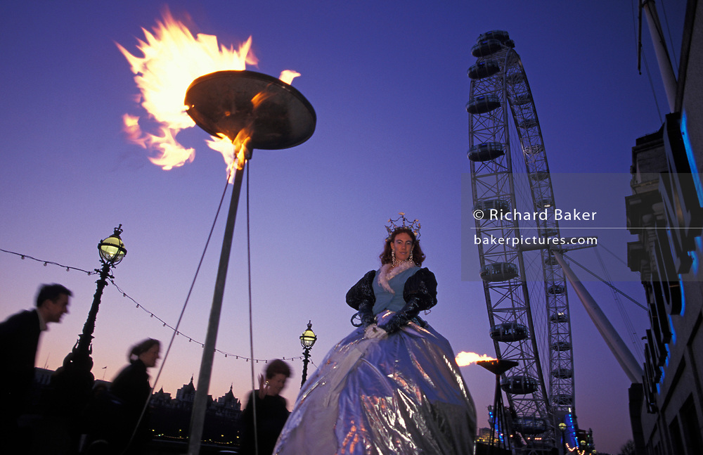 Months after the Millennium, a theatre group perform outside the London Aquarium on the Southbank and beneath a burning flame and the Millennium Wheel (later to be renamed The London Eye), on 6th April 2000, on the Southbank, London, England.