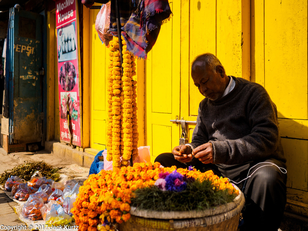 05 MARCH 2017 - KATHMANDU, NEPAL: A marigold garland vendor sells his flowers in front of a set of yellow doors in Kathmandu.     PHOTO BY JACK KURTZ