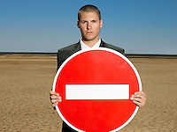 Businessman holding 'no entry' sign in desert half length