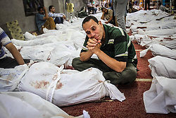 60360151 <br /> An Egyptian man sits near his dead relative s body in Al-Eman mosque, where 361 protester s bodies lay in lines, in Cairo s Nasr City, Egypt, Thursday Aug. 15, 2013. At least 421 were killed and 3,572 others injured across Egypt in clashes between supporters of ousted President Mohamed Morsi and the security troops, after the latter dispersed Wednesday two pro-Morsi sit-ins in the country, the Health Ministry said on Thursday.<br /> Picture by imago / i-Images<br /> UK ONLY