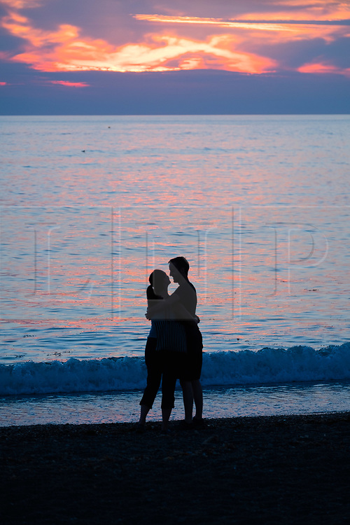 © Licenced to London News Pictures. Aberystwyth Wales UK, Thursday 26 July 2018. UK Weather: A young couple embrace romantically are  silhouetted by the setting sun over the sea in Aberystwyth at the end of a day of record breaking hot summer sunshine.  The UK wide heatwave continues, with little real respite from the very dry weather  despite some rain in the forecast for the weekend. Photo credit: Keith Morris/LNP