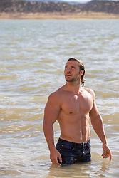 shirtless muscular man in a lake