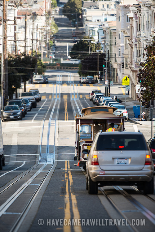 A cable car and car head down one of San Francisco's famous steep streets, with tracks for the cable car embedded into the road.