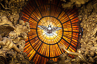 """A window of yellow alabaster is illuminated at its centre with an image of the Dove of the Holy Spirit.  This is above the Cathedra Petri or """"Chair of St. Peter"""" altar at St. Peter's Basilica.  The altar was created by Bernini.   Bernini created a large bronze throne in which it was housed, raised high on four looping supports held effortlessly by massive bronze statues of four Doctors of the Church, Saints Ambrose and Augustine representing the Latin Church and Athanasius and John Chrysostom, the Greek Church. The four figures are dynamic with sweeping robes and expressions of adoration and ecstasy."""
