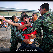 Volunteers retrain a devotee as he works himself into a frenzy during festivities at the Wat Bang Phra tattoo festival in Nakhon Chai Si province on the outskirts of Bangkok, Thailand.