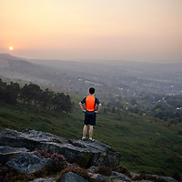 A photograph of a runner looking down a valley after running along the heathland of Ilkley Moor, Yorkshire, England