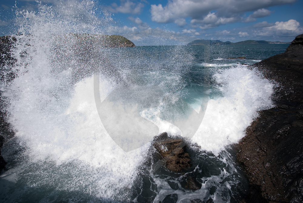 a crashing wave explodes on the rocky beach of cabo frio in rio de janeiro, brazil