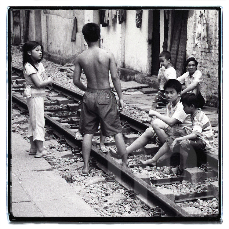 A group of young vietnamese kids sit on the railway of Hanoi. In this place, the train cross the city in front of house's doors.
