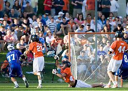 Virginia Goalie Bud Petit (8) dives to disrupt a shot by Duke defenseman Nick O'Hara (77).  The #3 ranked Virginia Cavaliers fell to the #2 ranked Duke Blue Devils 19-9 at the University of Virginia's Klockner Stadium in Charlottesville, VA on April 12, 2008.