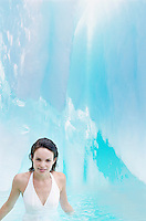 Woman standing in pool of water in ice crevice portrait