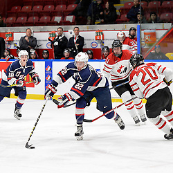 WHITBY, - Dec 18, 2015 -  Game #12 - Bronze Medal Game, Team Canada East vs. United States at the 2015 World Junior A Challenge at the Iroquois Park Recreation Complex, ON. Ross Colton #22 of Team United States tries to keep the puck from Matt Cairns #20 of Team Canada East during the first period.<br /> (Photo: Shawn Muir / OJHL Images)