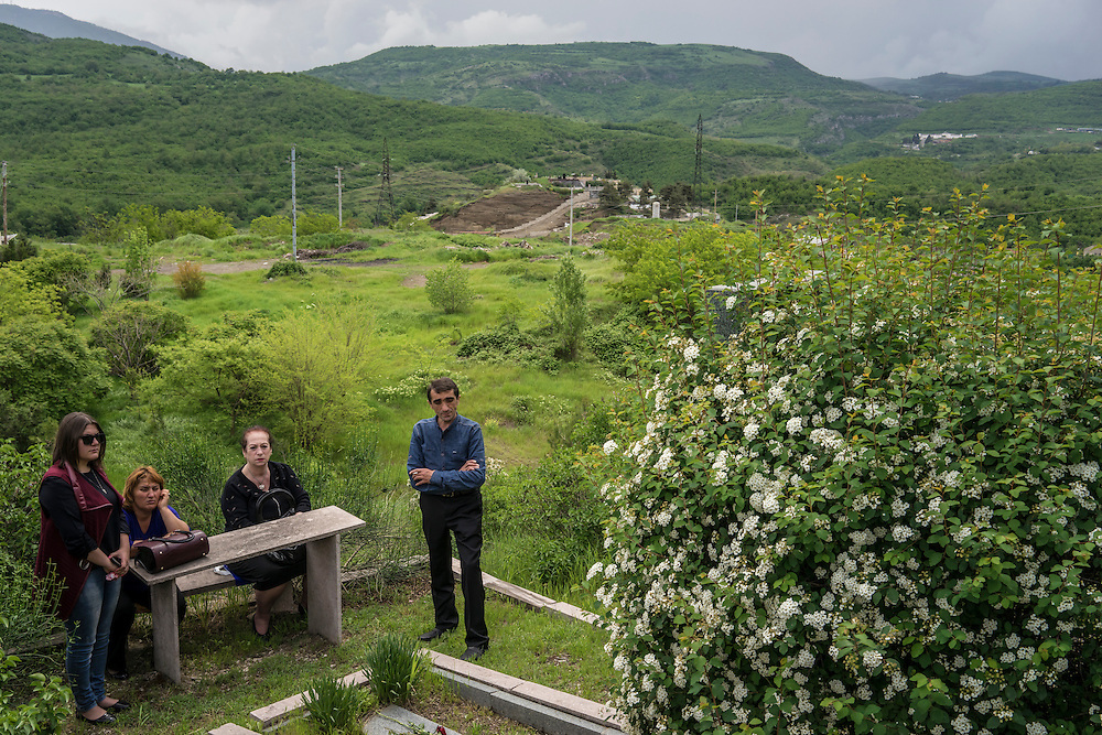 The family of a fighter killed in the 1990s war between Armenia and Azerbaijan gathers at his grave to mourn following a ceremony commemorating both the victory over Nazi Germany in the Second World War as well as the fall of the strategic town of Shushi to Armenian forces on Monday, May 9, 2016 in Stepanakert, Nagorno-Karabakh.