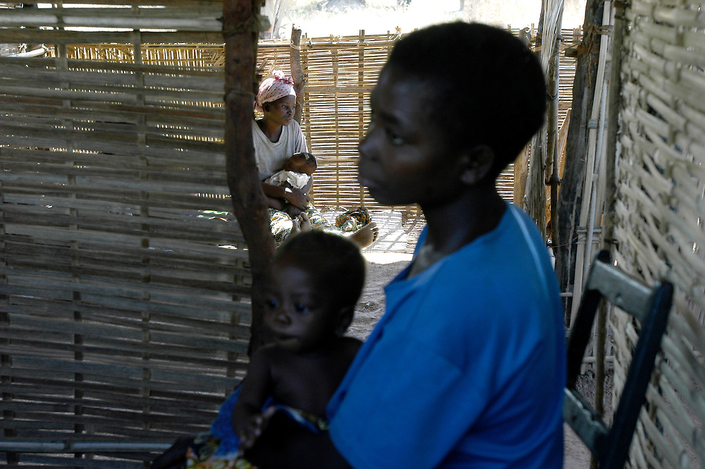 Mothers seek treatment for their sick children at a MSF mobile clinic in a remote village. Over 1200 people die every day in the RD Congo, primarily from preventable causes such as malaria, tuburculosis and malnutrition, as a direct result of the country's long conflict..Kintya, Democratic Republic of Congo. 21/06/2006.Photo © J.B. Russell