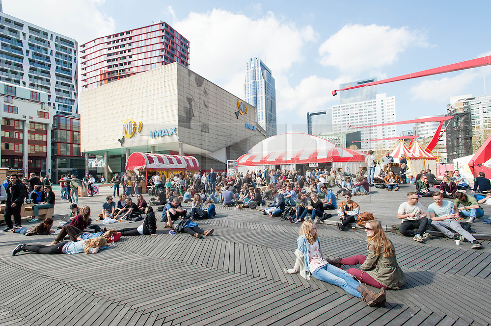 © Licensed to London News Pictures. 05/04/2014. Rotterdam, Netherlands.   Festival goers relax in sun alongside music venues at Motel Mozaïque Festival.   Motel Mozaïque  is an annual music/arts festival, held annually in Rotterdam, Netherlands.  Photo credit : Richard Isaac/LNP