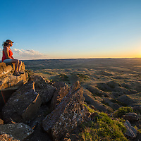 montana prairie one woman sitting on rock watching warm sunste