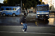ITALY, Rome, October 15, 2011:A protester runs away from Police vans during clashes in Rome, Saturday, Oct. 15, 2011.  © Christian Minelli/Emblema.