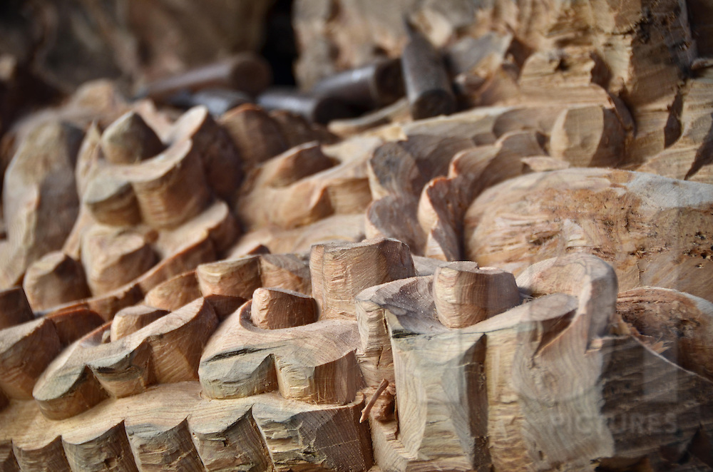Details of a wood sculpture with tools in the background, in Sapa surroundings, Lao Cai province, North Vietnam.