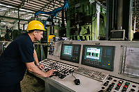 SANTA MARIA DEGLI ANGELI (ASSISI), ITALY - 11 JUNE 2018: A worker operates a steel flattening machine at the IRON S.p.A. factory, a publicly traded company that makes industrial steel parts, in Santa Maria degli Angeli (Assisi), Italy, on June 11th 2018.<br /> <br /> President Donald Trump's administration plans to impose tariffs on European steel and aluminum imports after failing to win concessions from the European Union, a move that could provoke retaliatory tariffs and inflame trans-Atlantic trade tensions. Until the moment that the American president rendered his decision, Mr. Capponi, the commercial director of IRON spa, was confident the continent would be spared.<br /> Given that IRON is a purchaser of steel, the company might benefit from the American tariffs. Steel now shipped to the United States from mills within Europe might stay here to avoid the tariffs, raising the supply and dropping prices. Chinese producers who export to American shores could divert their product to Europe, amplifying this trend.<br /> But Mr. Capponi was banking on none of this. Even if steel prices decline, his customers are likely to squeeze him for lower prices. More broadly, the American tariffs — justified by the Trump administration as a supposed defense of national security — reverberated as a blow against world trade.
