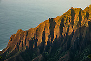 A golden sunset shines on cliffs of the Na Pali Coast above the Pacific Ocean, seen from Kalalau Lookout, Kokee State Park, Kauai, Hawaii, USA. Scenic Koke'e State Park is in northwestern Kauai in the Hawaiian Islands. Perched on a plateau between 3200 and 4200 feet, the park gets temperatures at least 15 degrees Fahrenheit cooler than at sea level. Koke'e receives 50-100 inches of rain per year, mostly from October to May. Its forests are dominated by Acacia koa and ohia lehua (Metrosideros polymorpha) trees.
