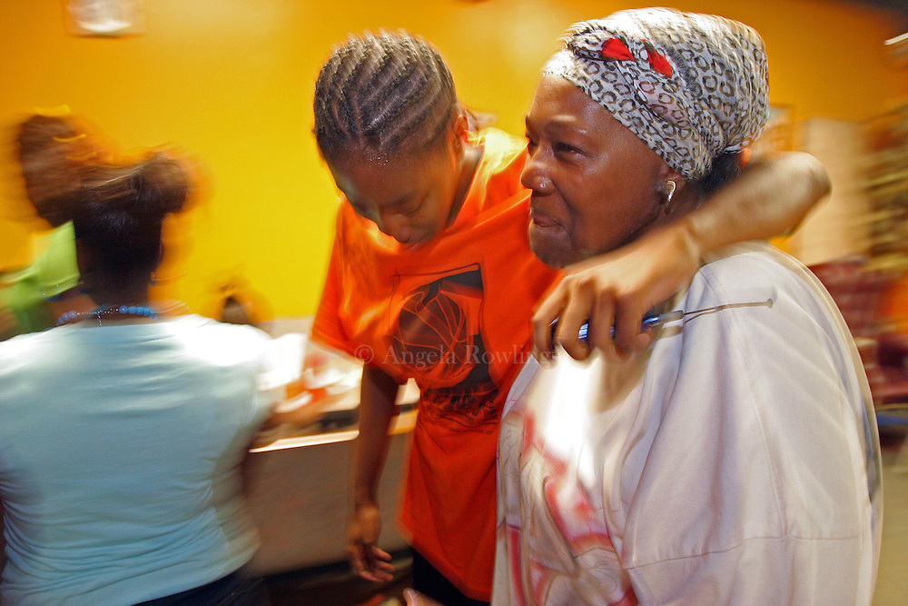 """(071107  Boston, MA)  Kamiya Flakes, 17, of Mattapan hugs """"Aunt"""" Greer Toney, the owner of Chez Vous, during the Be Smart program at Chez Vous in Mattapan, Wednesday,  July 11, 2007.   Toney says treats all the kids who enter Chez Vous as if they were her own family.  She frequently tells the kids she loves them, even as she occasionally reprimands them.  Staff photo by Angela Rowlings."""