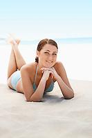 Young woman in bikini lying on beach