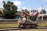 Railroad hand cart being pumped by a bunch of guys in Jesús Menéndez, Las Tunas Province, Cuba.