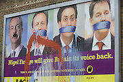 Splashed paint over the anti-EU membership 'UK Independence Party's (UKIP) political billboard that shows leader Nigel Farage (with daubed Hitler moustache) and a gagged Prime Minister David Cameron, Labour party leader Ed Milliband and (coaltion) Deputy PM Nick Clegg - all silent against a bullying European Union, seen in East Dulwich - a relatively affluent district of south London. The ad is displayed before European elections on 22nd May.