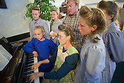 "Aug 10, 2008 -- COLORADO CITY:   Members of the Jessop family sing and play instruments in the living room of their home in Colorado City, AZ. The family has computers and cell phones but have chosen not to have televisions, instead they put on impromptu concerts nightly. They have more than 40 instruments in the house. The Jessops are polygamists and members of the FLDS. Colorado City and neighboring town of Hildale, UT, are home to the Fundamentalist Church of Jesus Christ of Latter Day Saints (FLDS) which split from the mainstream Church of Jesus Christ of Latter Day Saints (Mormons) after the Mormons banned plural marriage (polygamy) in 1890 so that Utah could gain statehood into the United States. The FLDS Prophet (leader), Warren Jeffs, has been convicted in Utah of ""rape as an accomplice"" for arranging the marriage of teenage girl to her cousin and is currently on trial for similar, those less serious, charges in Arizona. After Texas child protection authorities raided the Yearning for Zion Ranch, (the FLDS compound in Eldorado, TX) many members of the FLDS community in Colorado City/Hildale fear either Arizona or Utah authorities could raid their homes in the same way. Older members of the community still remember the Short Creek Raid of 1953 when Arizona authorities using National Guard troops, raided the community, arresting the men and placing women and children in ""protective"" custody. After two years in foster care, the women and children returned to their homes. After the raid, the FLDS Church eliminated any connection to the ""Short Creek raid"" by renaming their town Colorado City in Arizona and Hildale in Utah.     Photo by Jack Kurtz / ZUMA Press"