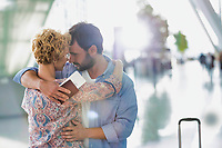 Husband embracing his wife in airport with lens flare